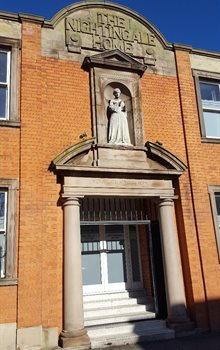 Colour photograph of the exterior of the Nightingale Home, Derby, featuring the sign and a statuette of Nightingale above a doorway.