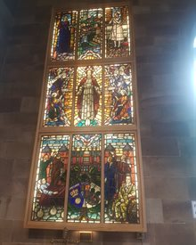 Stained glass window in St Peter's church featuring images of nurses and religious figures