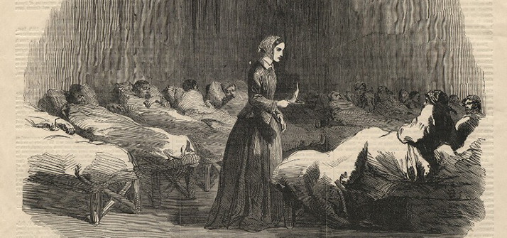1855 wood engraving of Nightingale wearing a shawl and carrying a candle, in a ward at Scutari hospital among the soldiers' beds.