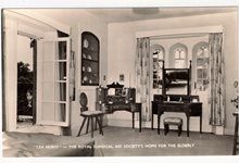 Black and white photograph of a room at Lea Hurst, including some 19th century style mahogany furniture.