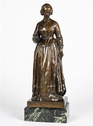 Miniature bronze statuette (maquette) of Nightingale based on the Walker statue in London. Nightingale is standing with her head turned demurely to the left and towards the ground.